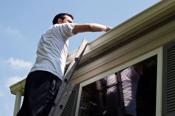 Young man on ladder cleaning house gutters
